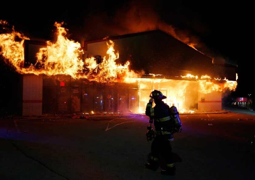 A firefighter walks past the burning Little Caesars restaurant in Ferguson, Mo., Monday night. Other stores in the area were looted.