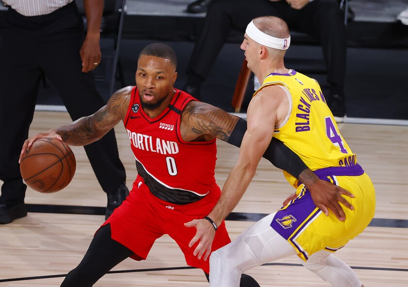 Portland Trail Blazers' Damian Lillard drives the ball against Lakers guard Alex Caruso.