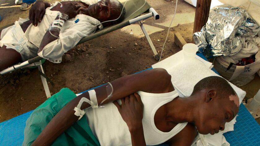 Two men suffering from cholera rest while receiving treatment at an emergency cholera clinic run by