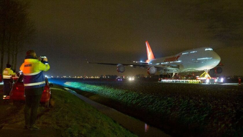 People take pictures as a self-propelled trailer transports a Boeing 747-400 plane through farmland from Schiphol Airport to a nearby hotel in Badhoevedorp, near Amsterdam, on Feb. 6, 2019. The jet is making its way, to its final resting place in the garden of a hotel.