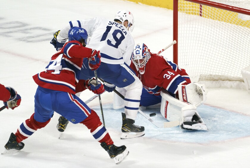 Montreal Canadiens goaltender Jake Allen makes a save off Toronto Maple Leafs' Jason Spezza as Canadiens' Phillip Danault looks on during the third period of an NHL hockey game in Montreal on Monday, April 12, 2021. (Paul Chiasson/The Canadian Press via AP)