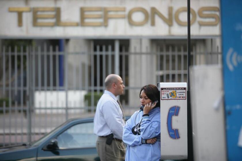 Fotografía de archivo del 16 de mayo de 2016 que muestra a una mujer hablando desde una cabina telefónica, en Ciudad de México (México). EFE