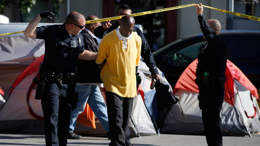 Police make an arrest during a skid row cleanup in April.
