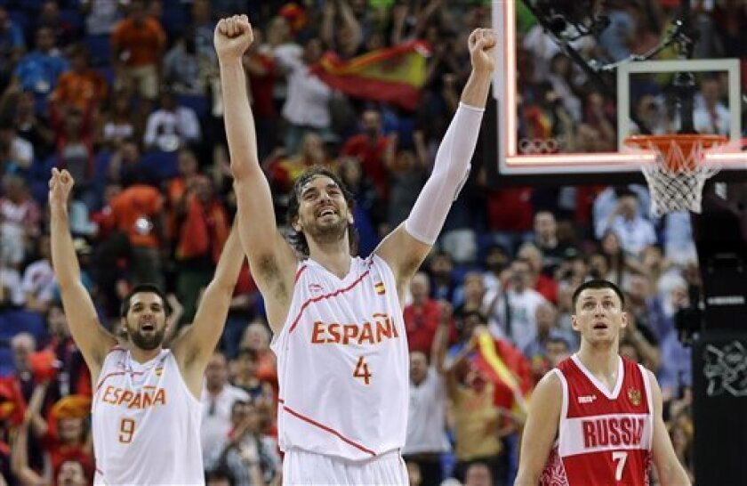 Spain's Pau Gasol (4) and teammate Felipe Reyes (9) celebrate their win over Russia in a semifinal men's basketball game at the 2012 Summer Olympics, Friday, Aug. 10, 2012, in London. Russia's Vitaliy Fridzon is at right.(AP Photo/Eric Gay)