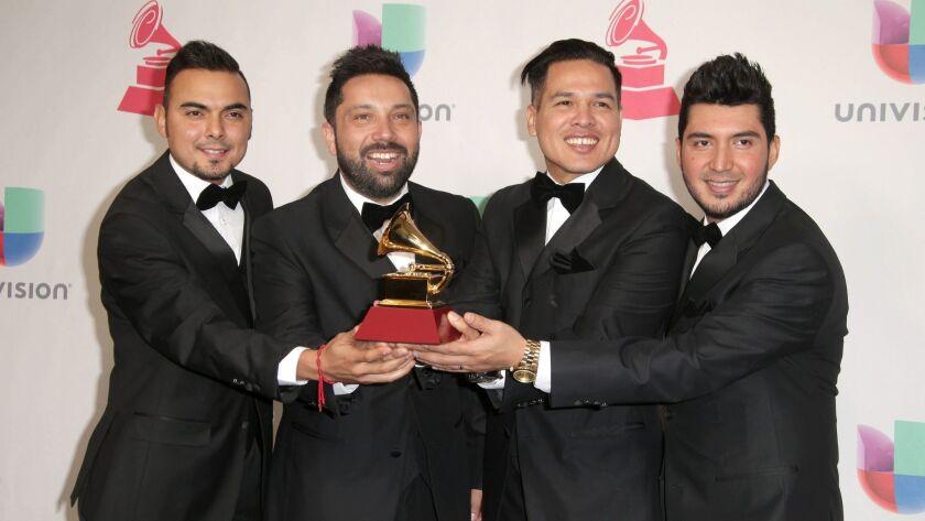 Members of Banda El Recodo de Cruz Lizarraga pose with their Latin Grammy for best banda album.