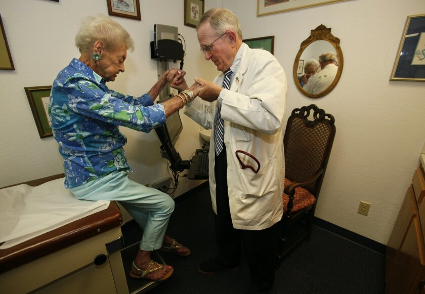 Dr. Doug Moir, a cardiologist in Escondido seen with patient Doris Dunn, questions how long he can afford his practice under new mandates. Peggy Peattie • U-T