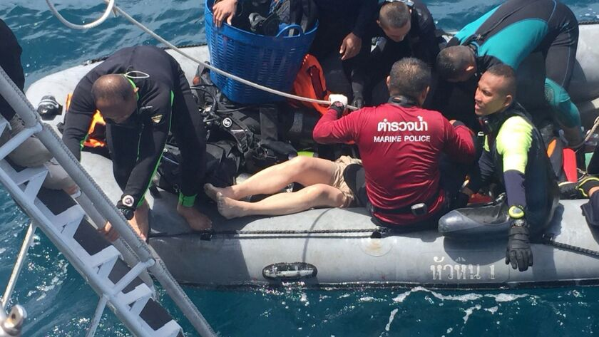 Divers on a rubber raft retrieve a body from a sunken tour boat off Phuket.