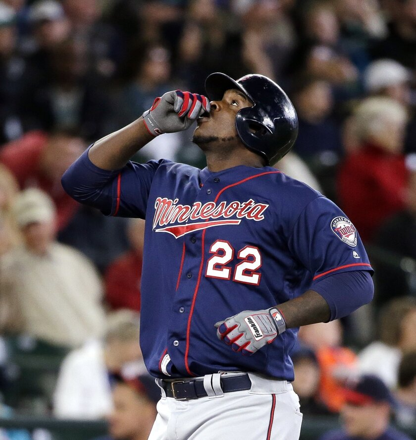 Minnesota Twins' Miguel Sano gestures before pointing skyward as he crosses home on his home run against the Seattle Mariners in the fourth inning of a baseball game Sunday, May 29, 2016, in Seattle. (AP Photo/Elaine Thompson)