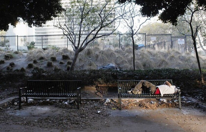 A man sleeps on a bench on the sidewalk surrounding the property across the street from City Hall. A building on the site was badly damaged in the 1971 Sylmar earthquake, and it's sat empty for decades.