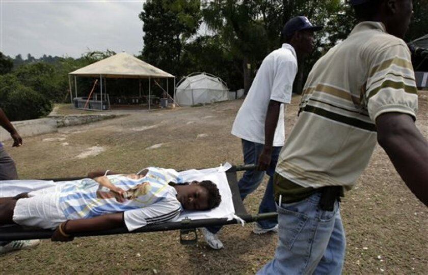 In this photo taken March 14, 2010, a woman is carried on a stretcher to receive medical attention at the field hospital run by the Jenkins-Penn Haiti Relief Operation, led by US actor Sean Penn, at the makeshift camp for earthquake survivors in the Petionville Golf Club in Port-au-Prince. Women, g