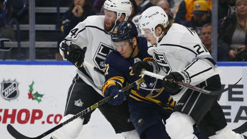 Buffalo Sabres forward Kyle Okposo, center, battles Los Angeles Kings' Derek Forbort, left, and Niki