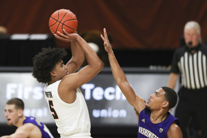 Oregon State's Ethan Thompson (5) shoots over Washington's Quade Green, front right, during the first half of an NCAA college basketball game in Corvallis, Ore., Thursday, Feb. 4, 2021. (AP Photo/Amanda Loman)