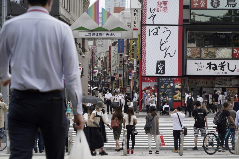An office worker carries a plastic bag as people stand before a pedestrian crossing near Ueno Station in Tokyo Friday, July 30, 2021. Japan is set to expand the coronavirus state of emergency in Tokyo to neighboring areas and the western city of Osaka on Friday in the wake of a record-breaking surge in infections while the capital hosts the Olympics. (AP Photo/Kantaro Komiya)