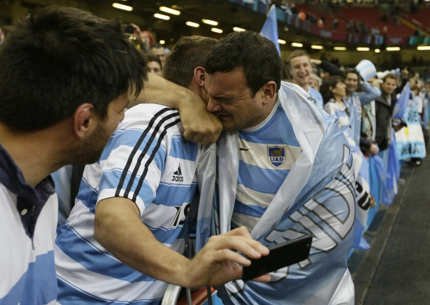 FILE - In this Oct. 18, 2015, file photo, Argentina's captain Agustin Creevy celebrates with a fan after winning the Rugby World Cup quarterfinal match between Ireland and Argentina at the Millennium Stadium, Cardiff. Despite an unavoidably hectic travel schedule, Argentina's stocks in world rugby
