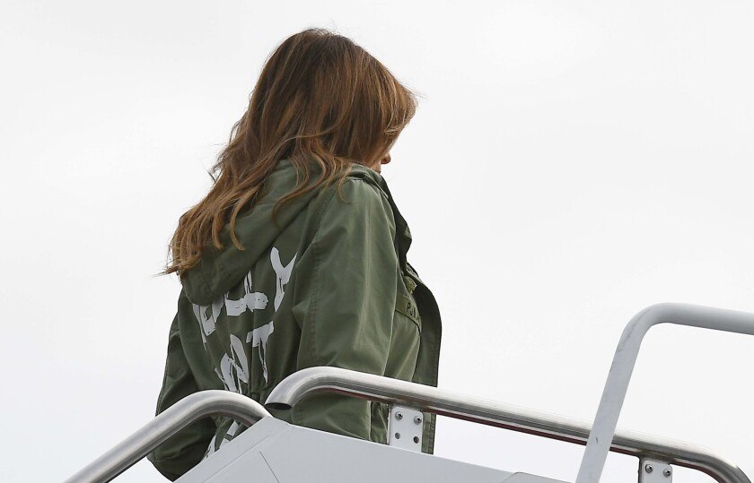 "Melania Trump boards a flight in June 2018 wearing a jacket that reads: ""I really don't care. Do U?"" in white lettering."