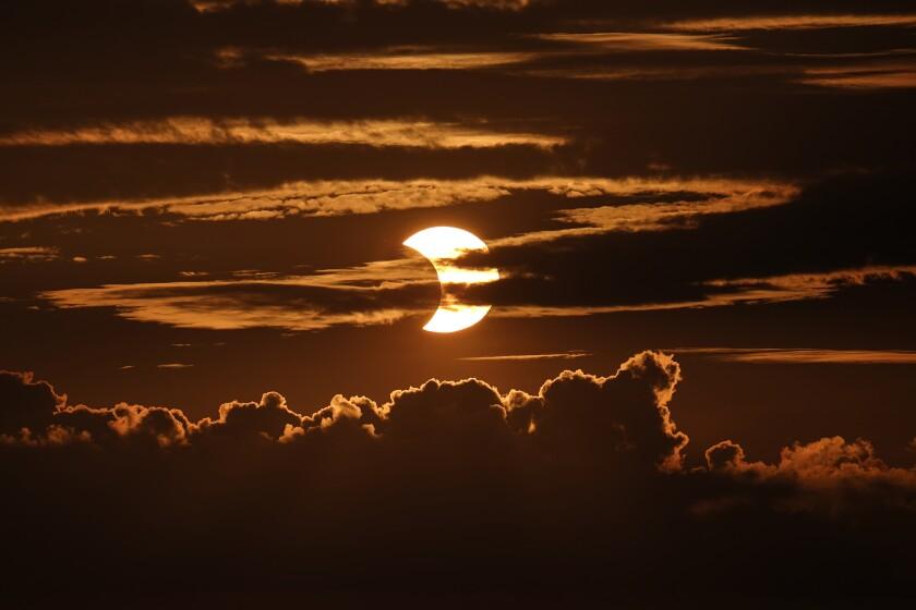 Un eclipse solar parcial asoma tras las nubes en Arbutus, Maryland, EEUU, jueves 10 de junio de 2021.