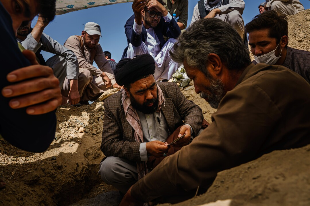 Imam Nor Aqa Mossani, 40, reads a religious scripture as relatives of Mushtaq carry out his funeral on Martyrs Hill