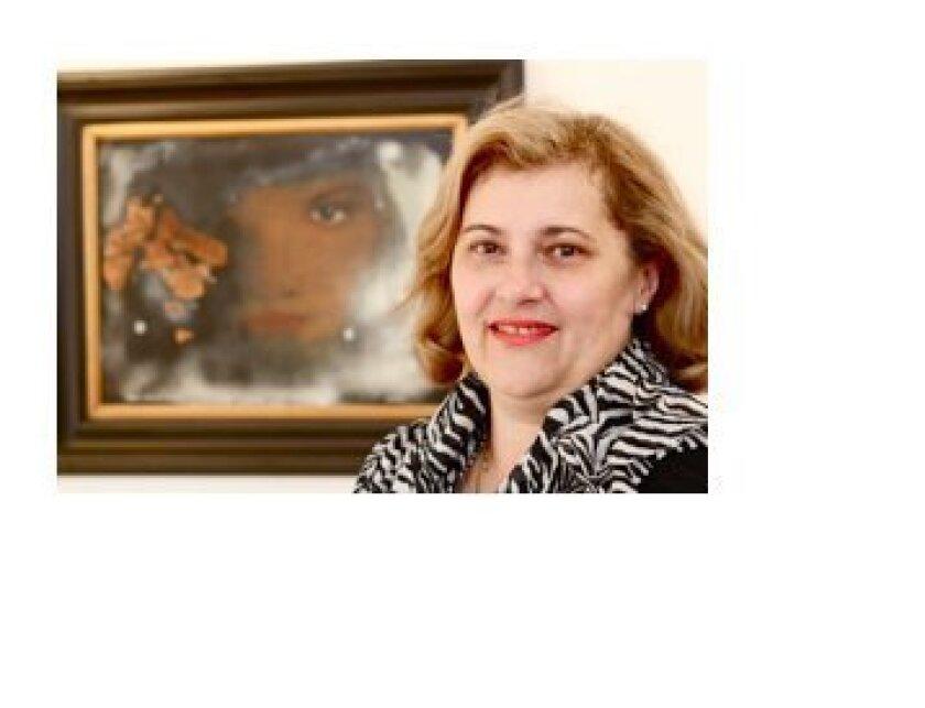 """Biljana Beran in front of her portrait by Jan Beran, """"Inside Looking Out"""", Mix Media on Wood, 2010. Photo: Richard Tiland"""