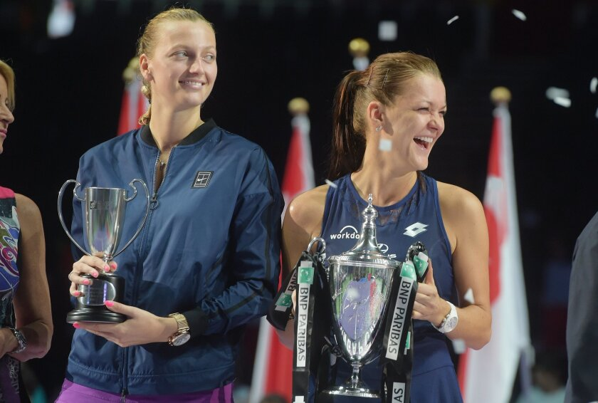 Agnieszka Radwanska of Poland, right, and Petra Kvitova of the Czech Republic, left, hold their trophies at the victory ceremony after Radwanska won their singles final match at the WTA tennis finals in Singapore on Sunday, Nov. 1, 2015.  (AP Photo/Joseph Nair)