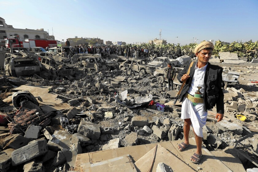 In Sana, Yemen, an armed Houthi rebel keeps watch near vehicles reportedly destroyed by airstrikes led by Saudi Arabia.