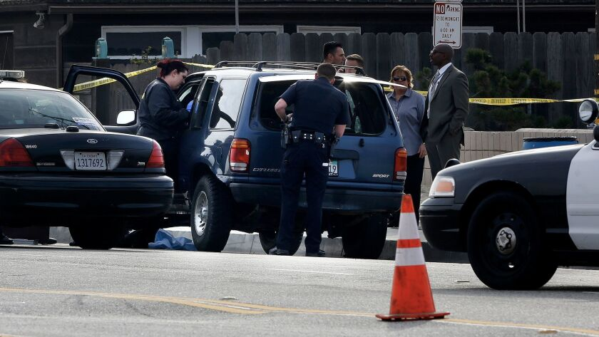 Investigators search an SUV where a second body was found near the 5400 block of East Ocean Boulevard in Long Beach.