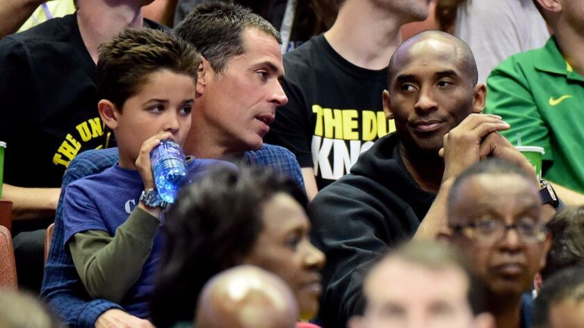 Rob Pelinka talks with Kobe Bryant during an NCAA men's basketball tournament game at Honda Center on March 26, 2016.