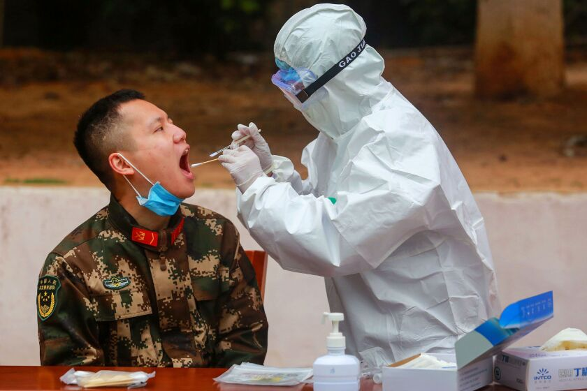 A Chinese paramilitary police officer is tested for the COVID-19 infection in Shenzhen in Guangdong province