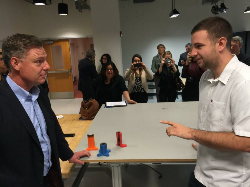 US Rep. Scott Peters (left) meets UC  San Diego student Kyle Adriany during a tour of the Qualcomm Institute on Tuesday. On the table are pieces of a rocket made by a 3D printer for the Adriany's start-up, Additive Rocket Company.