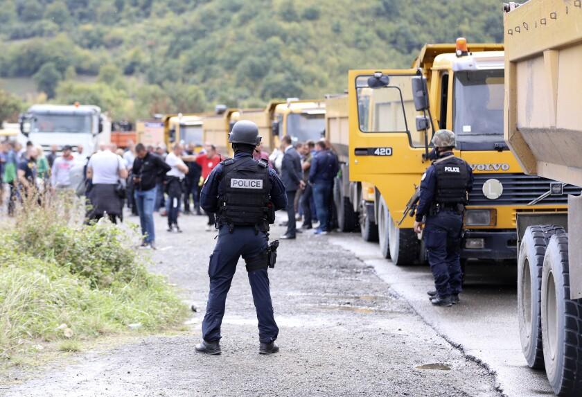 La policía de Kosovo se encuentra en el camino hacia el cruce fronterizo de Jarinje, 20 de septiembre de 2021. Aumentan las tensiones entre los dos países porque Kosovo aplica una norma de quitar las placas a los autos que llegan de Serbia. (AP Foto/Bojan Slavkovic)