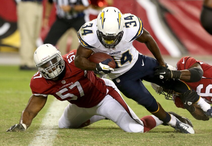 San Diego Chargers running back Fozzy Whittaker (34) scores a touchdown as Arizona Cardinals linebacker Alex Okafor (57) and Curtis Taylor (26) defends during the first half.
