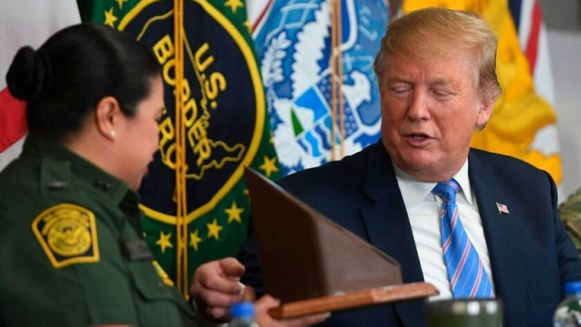 President Trump is presented with a souvenir piece of border barrier by Border Patrol agent Gloria Chavez during a discussion of immigration and border security April 5 in Calexico.