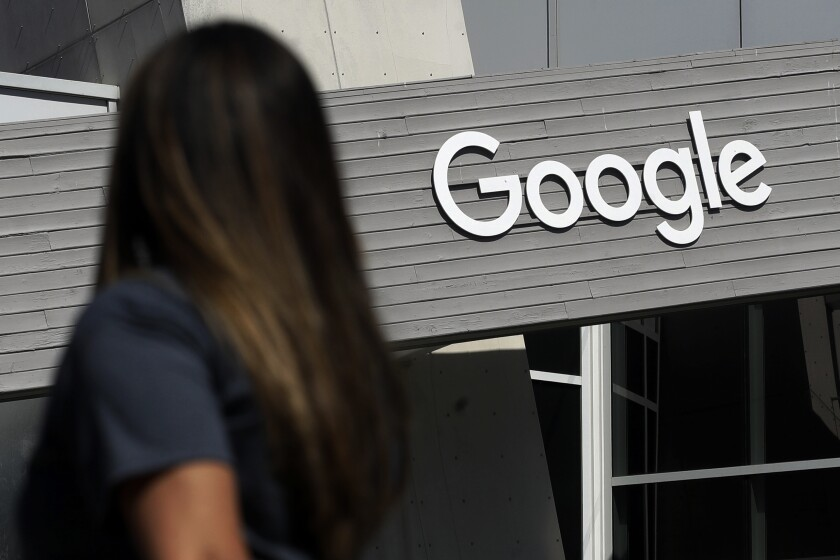 FILE - In this Sept. 24, 2019, file photo, a woman walks below a Google sign on the campus in Mountain View, Calif. On Wednesday, May 5, 2021, Google said that it expects about 20% of its workforce to still work remotely after the pandemic. In addition, some 60% will work a hybrid schedule that includes about three days in the office and two days wherever the employees work best. (AP Photo/Jeff Chiu, File)