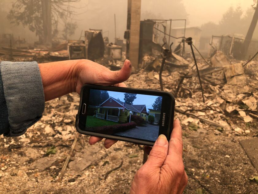 Mary Chenault holds a photo of her home in Lyons, Ore., before a wildfire reduced it to ruins.