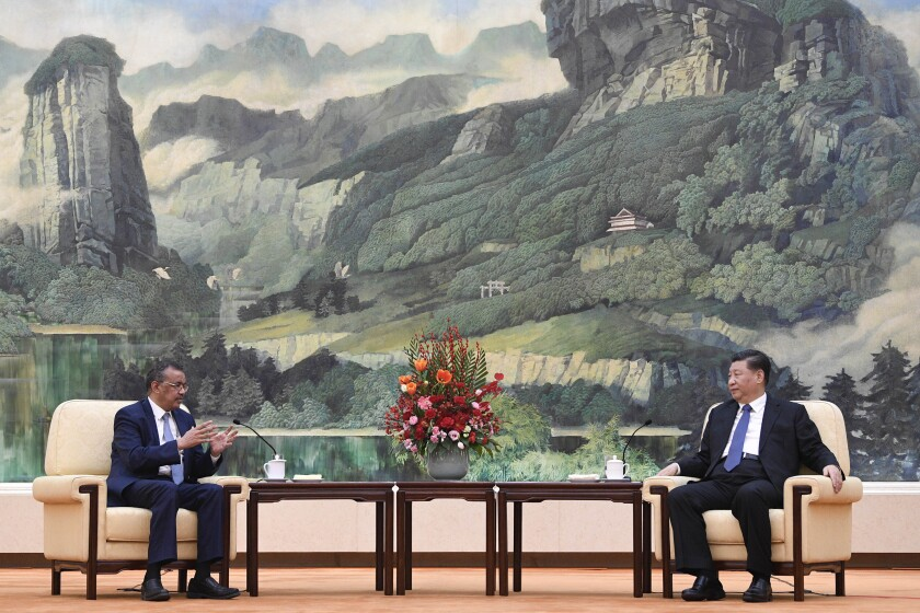 """FILE - In this Jan. 28, 2020, file photo, Tedros Adhanom Ghebreyesus, director general of the World Health Organization, left, meets with Chinese President Xi Jinping at the Great Hall of the People in Beijing. Throughout January, the World Health Organization publicly praised China for what it called a speedy response to the new coronavirus. It repeatedly thanked the Chinese government for sharing the genetic map of the virus """"immediately"""" and said its work and commitment to transparency were """"very impressive, and beyond words."""" But behind the scenes, there were significant delays by China and considerable frustration among WHO officials over the lack of outbreak data, The Associated Press has found. (Naohiko Hatta/Pool Photo via AP, File)"""