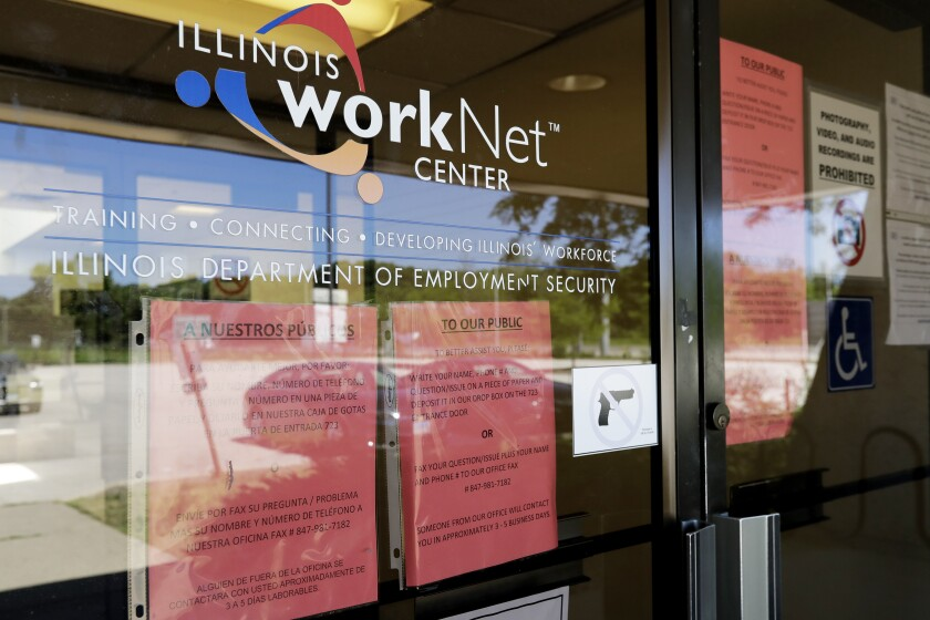 Signs are displayed at the closed Illinois Department of Employment Security WorkNet center in Arlington Heights, Ill.