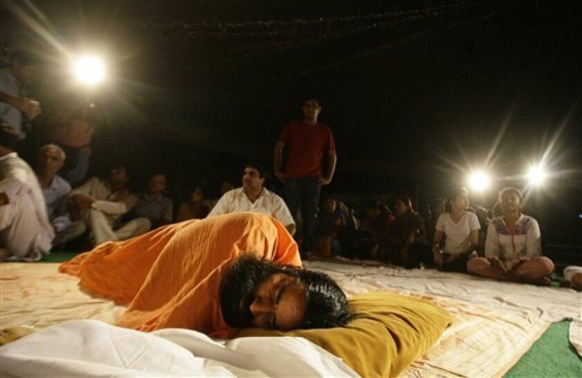 Indian yoga guru Baba Ramdev sleeps on a stage as he continues his protest hunger strike at his ashram, or spiritual headquarters, in Haridwar, India, late Sunday, June 5, 2011. Indian police fired tear gas early Sunday to break up a hunger strike by the charismatic yoga guru demanding an end to endemic corruption, forcibly removing him and thousands of his followers. Authorities flew Ramdev from New Delhi back to his hometown after detaining him earlier in the day. (AP Photo/Pankaj Nangia)
