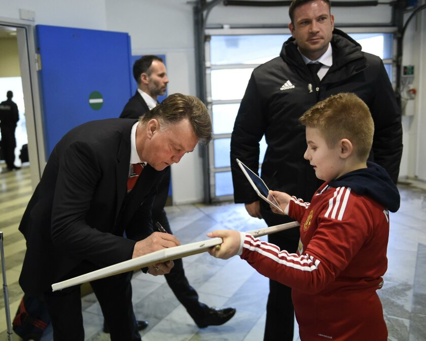 Manchester United  manager Louis van Gaal  signs an autograph  after arriving at Karup Airport, Denmark on Wednesday, Feb. 17 2016. United will play Danish team  FC Midtjylland in a Europa League soccer match on Thursday.  (Lars Poulsen, POLFOTO via AP ) DENMARK OUT