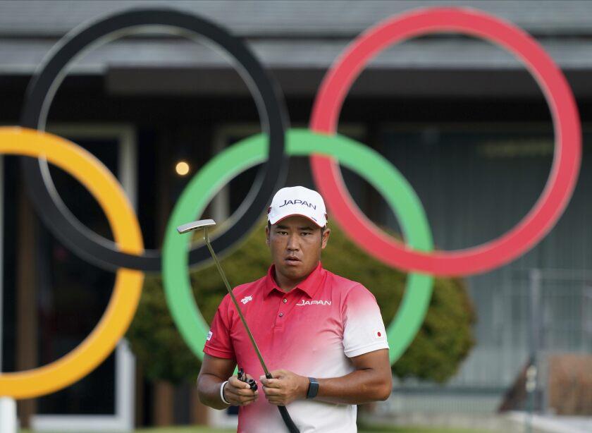 Hideki Matsuyama holds a golf club at the Tokyo Olympics.