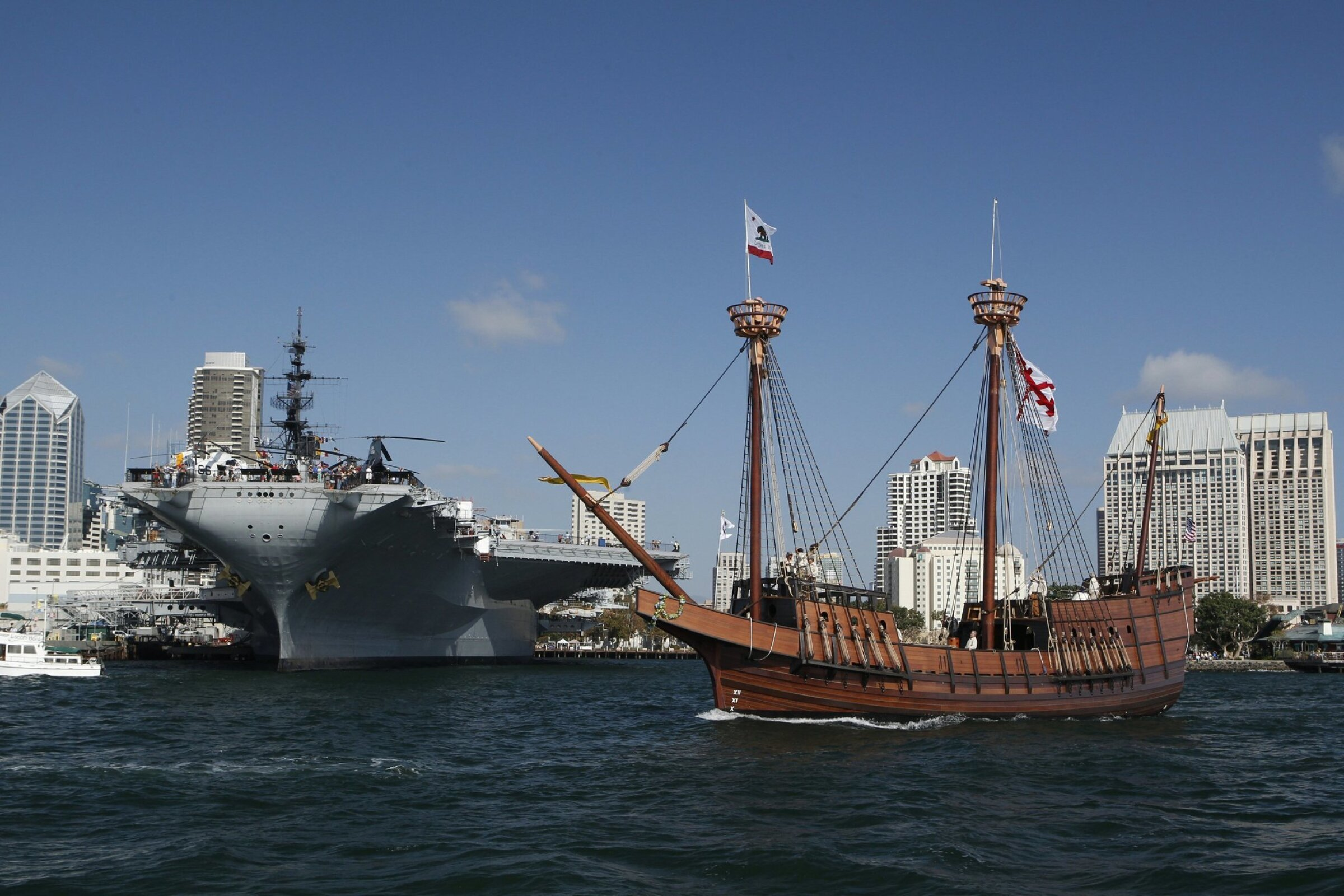 The Maritime Museum of San Diego's replica of the San Salvador sails past the USS Midway Museum. The Maritime Museum and the USS Midway Museum are both open on July 4.