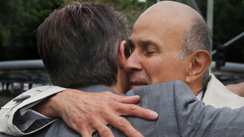 Former Los Angeles County Sheriff Lee Baca hugs his lawyer, Nathan Hochman, outside court last month.