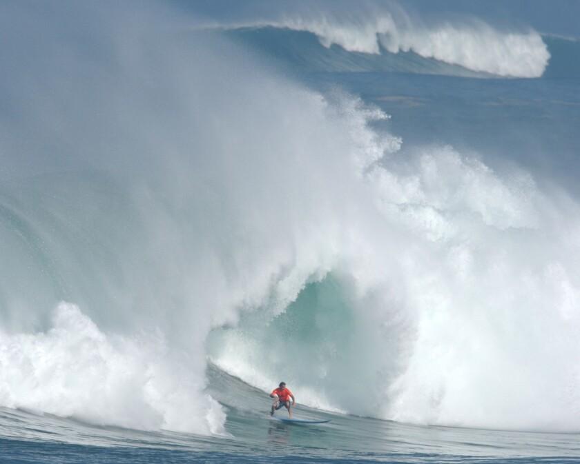 A surfer catches a big wave