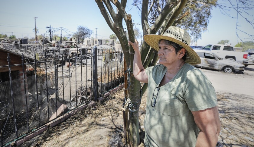 Ana Valenzuela stares at the pile of ashes and debris where her home in Niland, Calif., once stood.