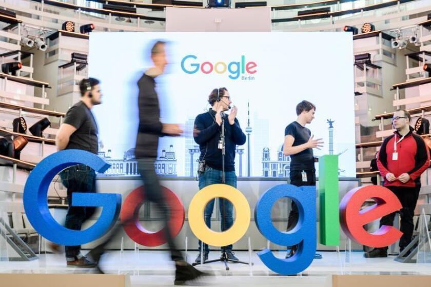 Empleados junto al logotipo de la multinacional estadounidense Google. EFE/ Clemens Bilan/Archivo