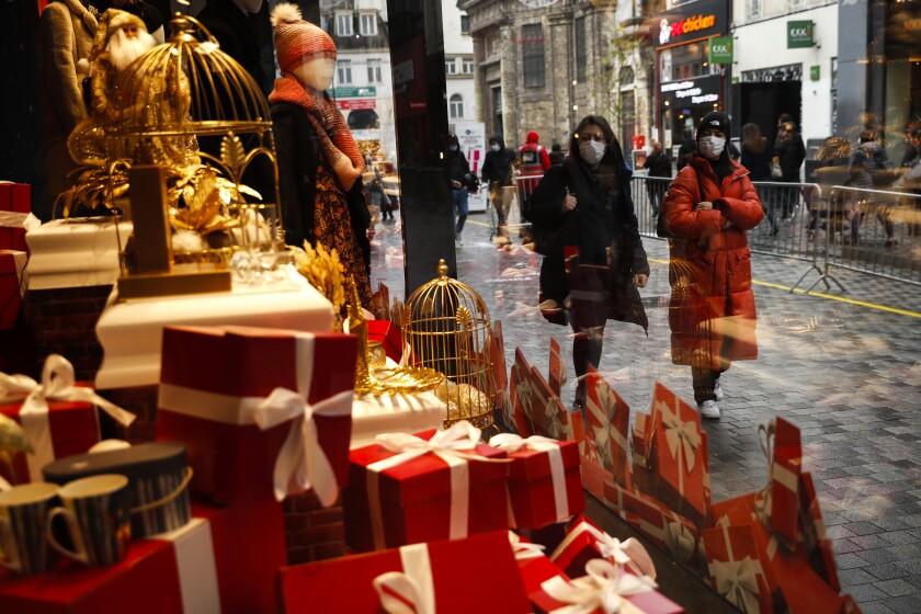 Transeúntes, luciendo máscaras contra el coronavirus, pasan junto a la vidriera de una tienda