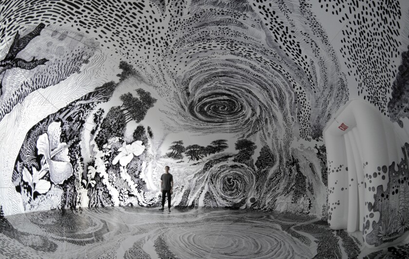 """Oscar Oiwa stands inside his immersive installation """"Dreams of the Sleeping World."""""""