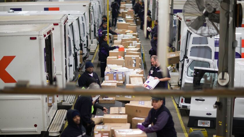 Workers sort packages on a conveyor belt before loading them onto trucks for delivery at a FedEx facility in Marietta, Ga., in 2014.