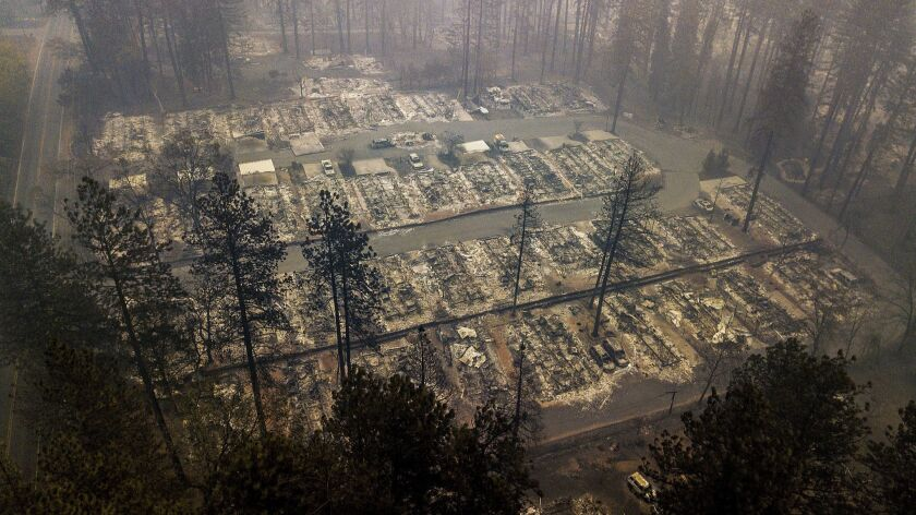 FILE - In this Thursday, Nov. 15, 2018, file photo, residences leveled by the wildfire line a neighb