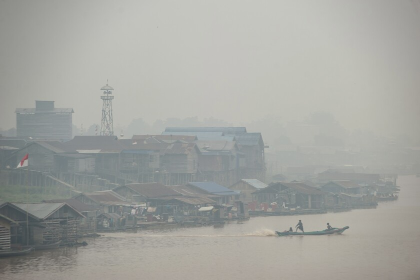 Haze from forest fires blankets villages along Kahayan river in Palangkaraya, Central Kalimantan, Indonesia, Friday, Sept. 20, 2019. Haze blown by monsoon winds from fires in Indonesia has begun affecting some areas of the Philippines and raised concerns about aviation safety and possible health risks, an official said Friday. (AP Photo/Fauzy Chaniago)