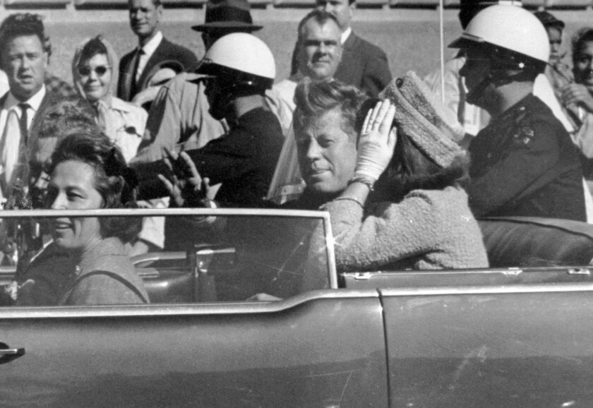 President John F. Kennedy waves from his car in a motorcade in Dallas just before being shot on Nov. 22, 1963.