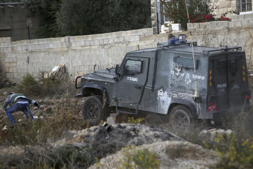 In this Friday, Oct. 30, 2015 photograph, an Israeli police jeep charges towards a Palestinian demonstrator, who was hit by the jeep moments later, beaten and arrested during clashes outside Ramallah, West Bank. Recent video has shown Israeli troops shooting a Palestinian lying in a street from clo